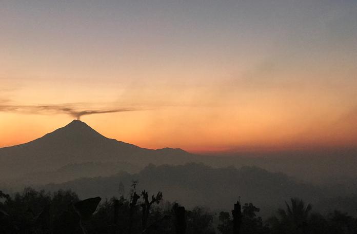Amanhecer na salva de Java com vulcão ativo ao fundo