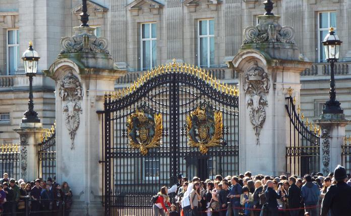 A multidão se aglomera ao lado dos portões de Buckingham