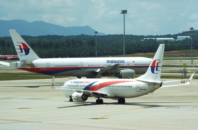 Boeing 737 taxiando próximo a um Boeing 777 já aposentado